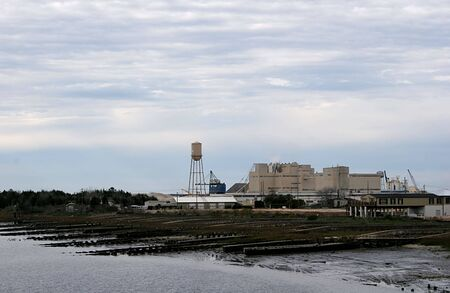 A paper factory on the coast against cloudy skies