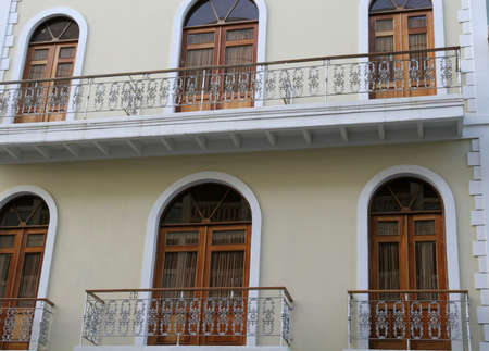 verandas: Classic wrought iron verandas on an old stucco building