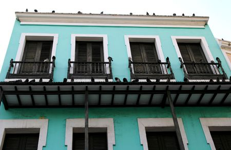 Pigeons roosting on an old green stucco building Stock Photo - 836312