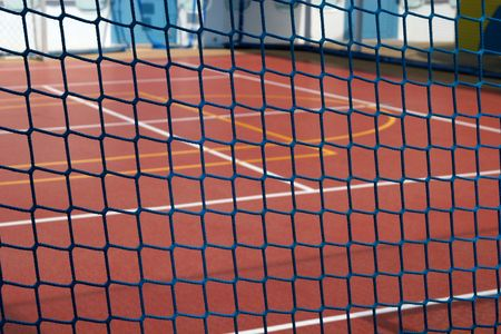 cattle grid: Blue rope fence in focus with basketball court in background
