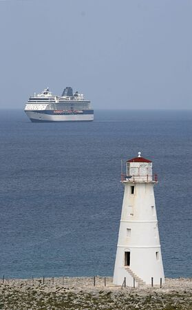 Old lighthouse on point with cruise ship in background Stock Photo - 850124