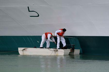 배의 선체를 그리는 두 노동자