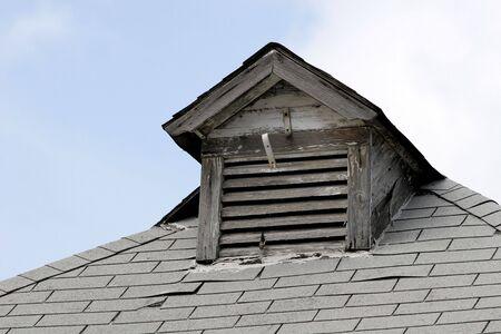 dormer: Old rustic dormer and roofline on a city building