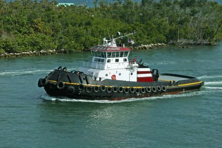 Large tug boat cruising up the channel Stok Fotoğraf