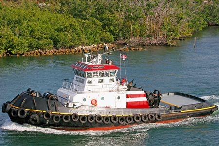 Colorful tugboat cruising up the intracoastal waterway