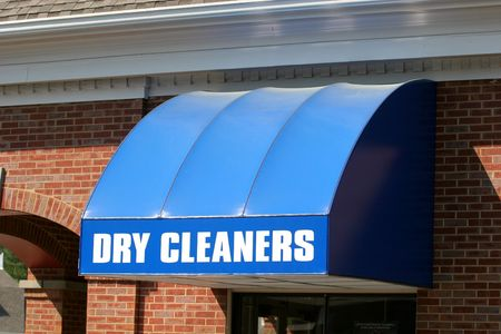 A bright blue canopy over a dry cleaners window