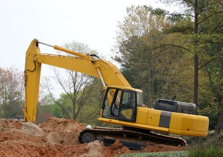 front end loader: A front end loader atop a pile of dirt