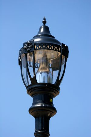 An old fashioned street lamp against a blue sky