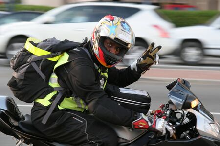 A man on a fast motorcycle flashing peace