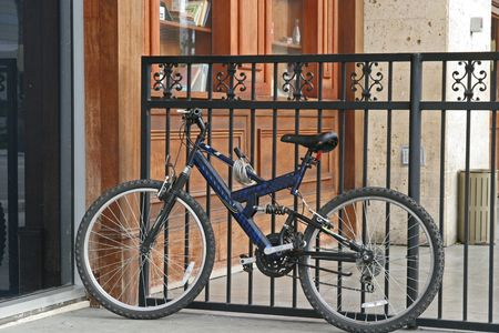 A black bike leaning against a black iron fence Stock Photo - 950395
