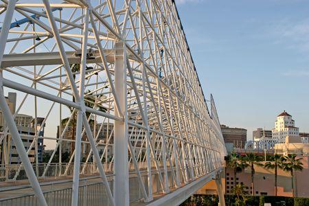 pedestrian walkway: A white steel bridge spanning a pedestrian walkway