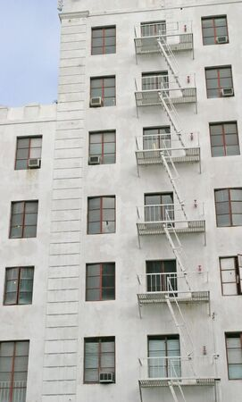 A white fire escape on the side of a white building