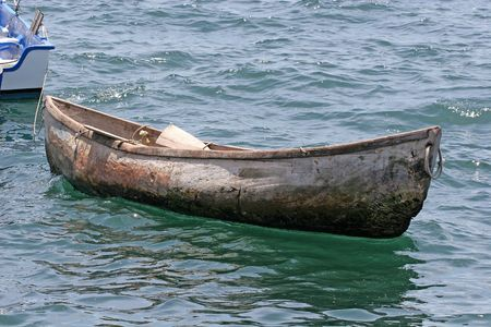 �ber Wasser: Eine alte h�lzerne Kanu, die in der Bucht flott