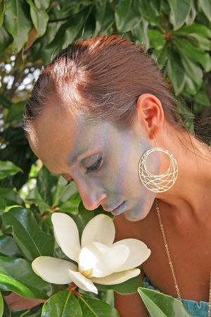 Beautiful model with exotic makeup smelling magnolia blossom photo