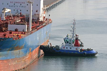 Pilot boat guiding a tanker into a port photo