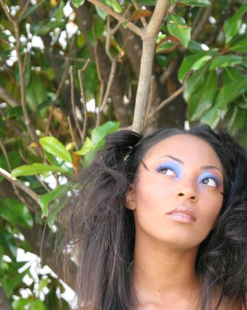 A makeup model in natural setting looking up photo