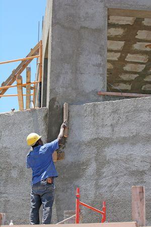 bloque de hormigon: Un hombre que trabaja en la capa de una pared concreta del bloque