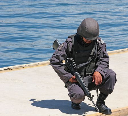 Mexican soldier kneeling on a dock with automatic weapon