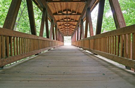 Old wooden bridge in a forest into the light