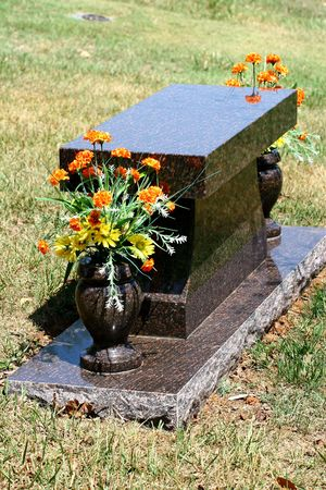 A polished marble headstone and flowers in a cemetery Stock Photo