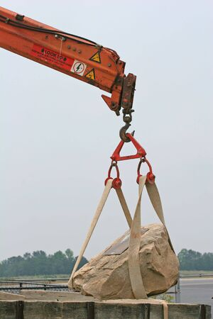 heavy industry: A construction crane lifting a heavy rock in place