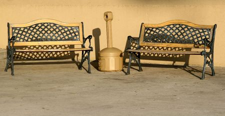 designated: Two benches and an ashtray set up at a designated outdoor smoking area