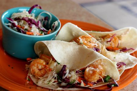 Three shrimp tacos and slaw on colorful plates photo