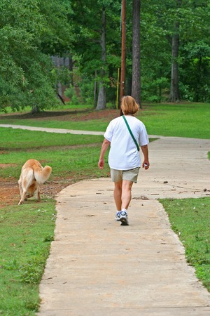 retreiver: A woman walking a golden retreiver dog in a park Stock Photo
