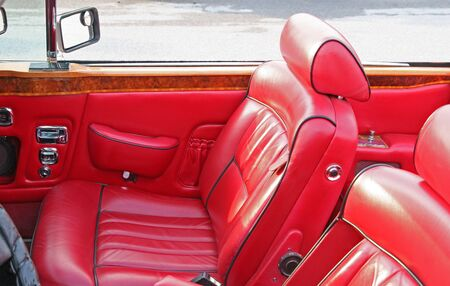 A classic antique car with red leather interior