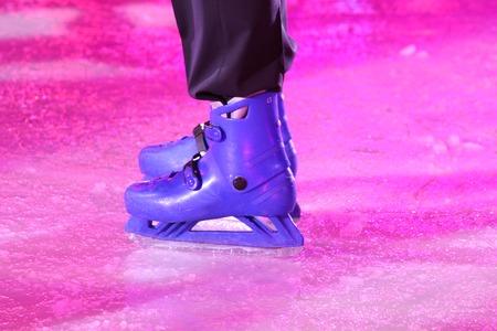 slushy: Black pants over blue skates on slushy ice lit by a purple spot