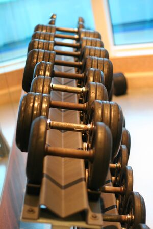A weight rack in a gym showing rows of dumbbells