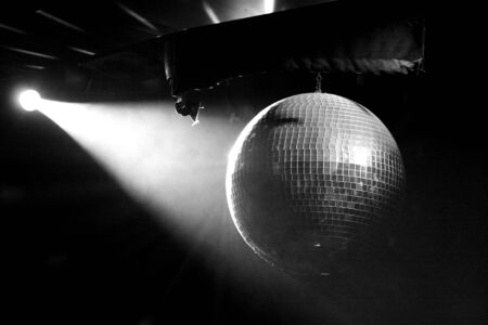 A lit mirrored disco ball in smoky room in black and white photo