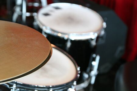 Close up of cymbals with a drum set in the background