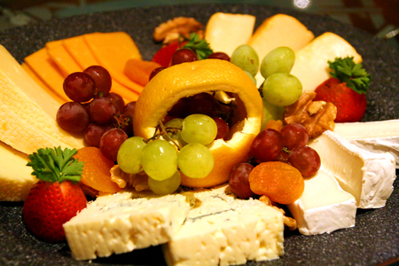 A deli tray of fresh fruit and fine cheese