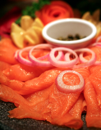 A platter of smoked salmon with onions and capers