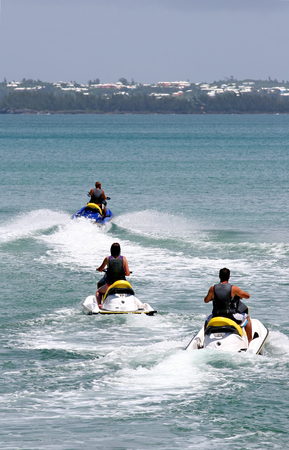 Jet skiers speeding out across the bay