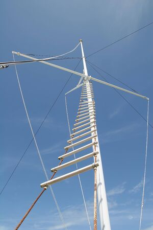A white rope ladder ascending up the mast of a ship