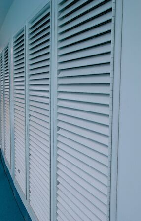louvered: A row of blue louvered doors into the distance Stock Photo