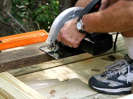 Een timmerman snijden een stuk van hout met een cirkelzaag