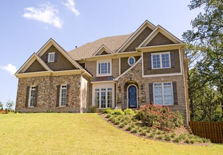 A nice stone and brick house on a landscaped hill