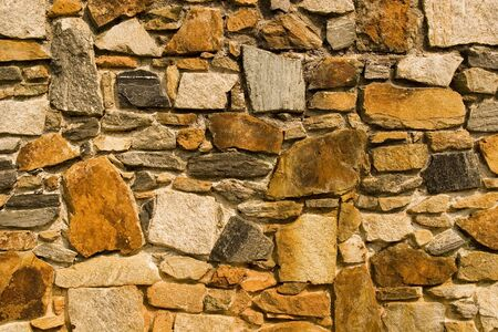 wall textures: An old stone wall with rust colored rocks and mortar Stock Photo