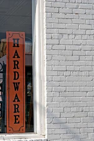 shop sign: An old white brick hardware store with sign in the window