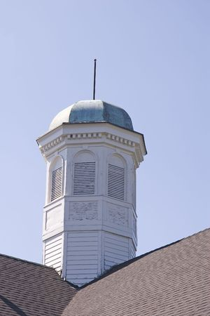 An old and tarnished cupola against blue sky