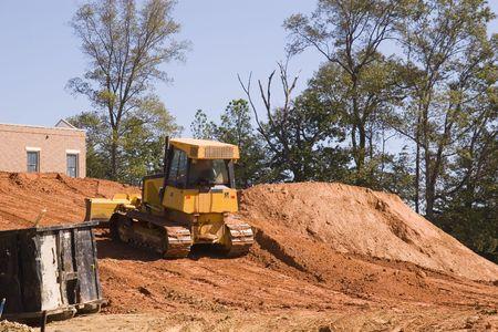 jobsite: A bulldozer pusing dirt onto a hill