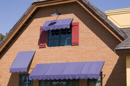 awnings: Purple Awnings on a Red Brick building Stock Photo