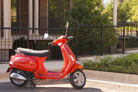 A small bright red scooter on a sidewalk