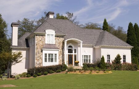 A nice stone and stucco house on a grassy hill