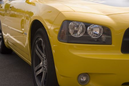 The front quarter of a classic yellow muscle car Фото со стока