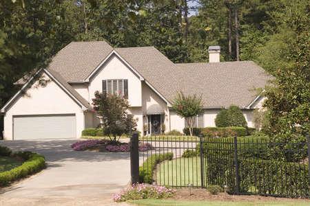 stucco house: A nice stucco house behind an iron fence