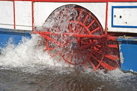 churning: A red paddle wheel on a boat churning through the water